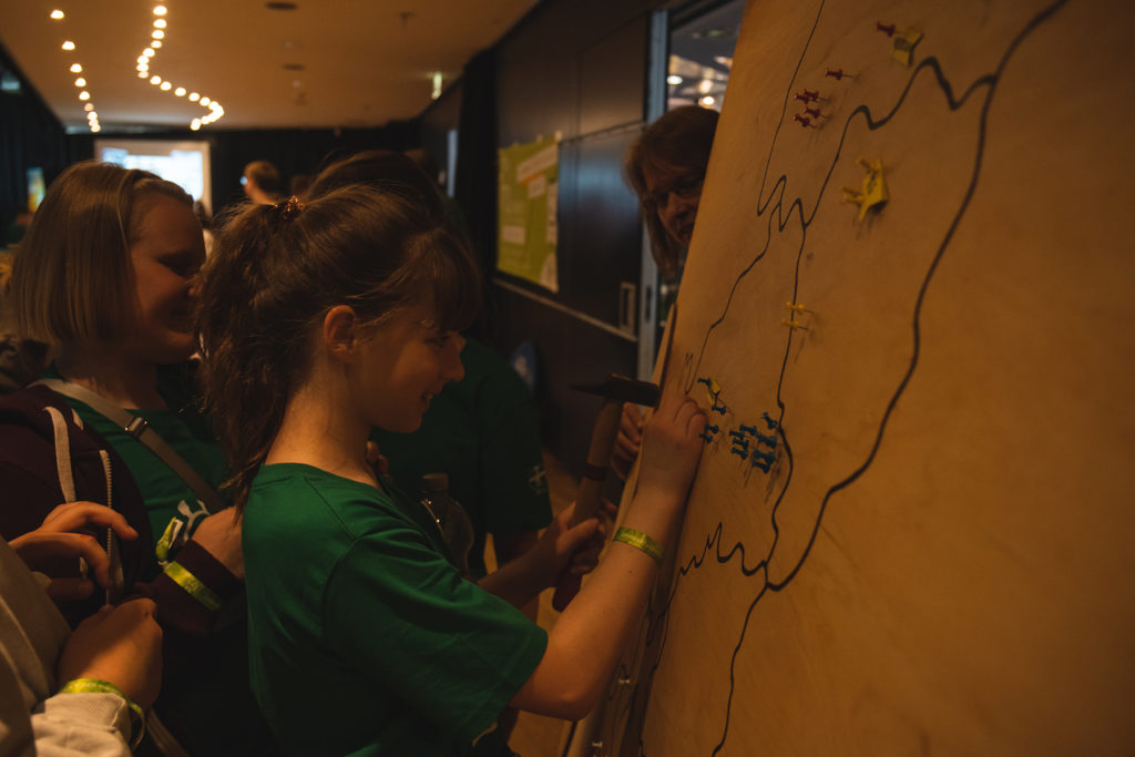 Ein Mädchen pinnt ihren Aktionsort auf die Bistumskarte.